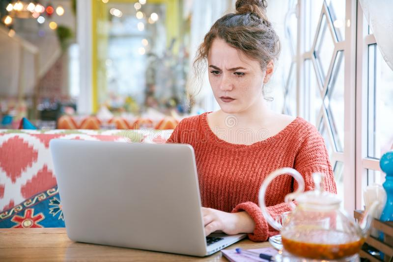 Young curly redhead girl with freckles on the skin with a serious puzzled expression looking at a laptop royalty free stock photo