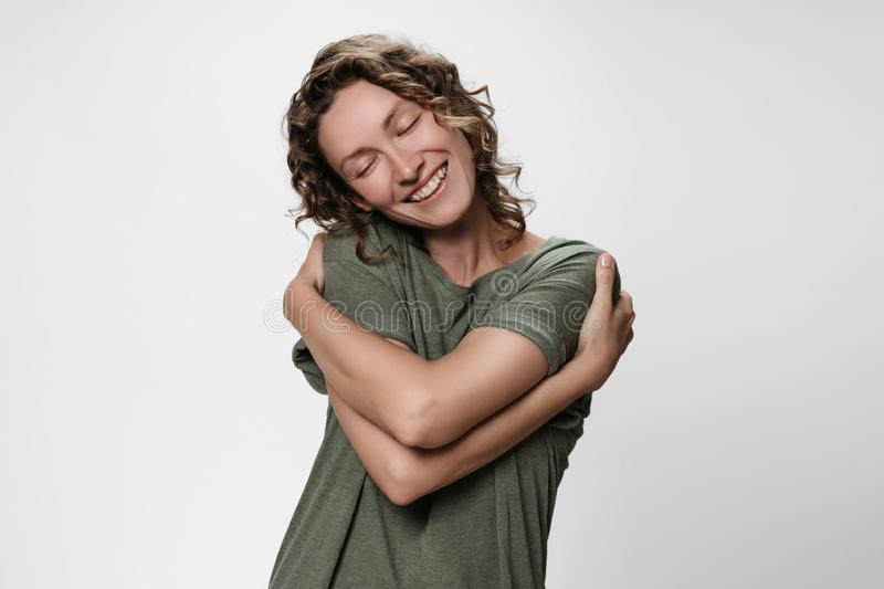 Young curly woman hugging herself, looks happy, expresses natural positive emotions stock photo