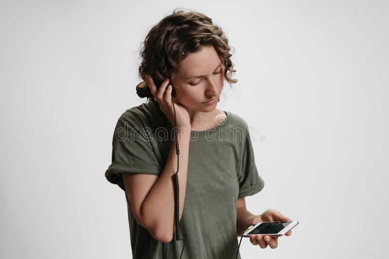 Young curly woman leisure, hold her modern stereo headphones. Choose audio in music app, listen favorite playlist, satisfied with quality of sound. Isolated royalty free stock photography