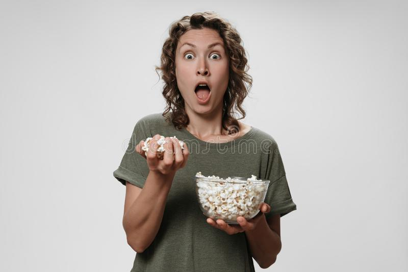 Young curly woman opens eyes and mouth widely eating popcorn, watching a movie or TV royalty free stock photos