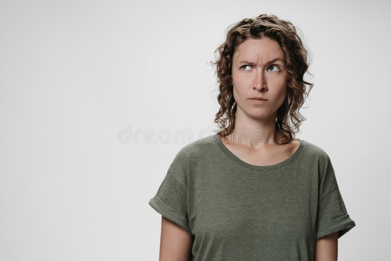 Young curly woman with puzzled raises eyebrows negative facial expression. Thinks fie, disapprovingly sees something disgusting and unpleasant, stands agaist royalty free stock images