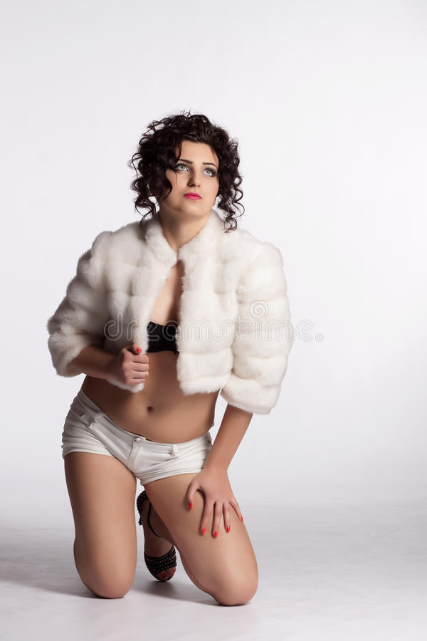 Young Curly Woman In White Fur Coat, Shorts, Black Bra And ...