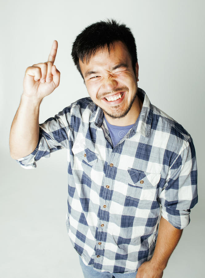 Young cute asian man on white background gesturing emotional, pointing, smiling, lifestyle people concept stock photos