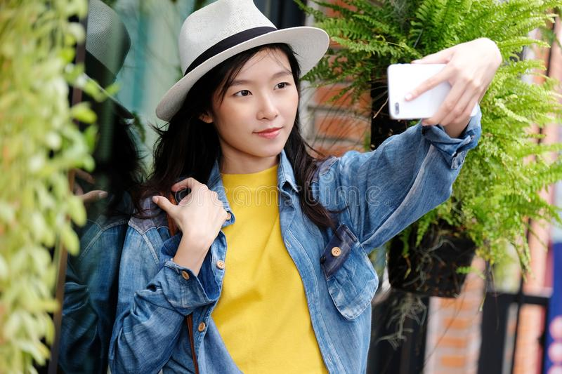 Young cute asian woman in casual style making selfie with her smartphone in the urban city outdoors background, woman selfie, stock image