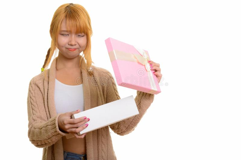 Young cute Asian woman opening gift box looking disappointed stock photo