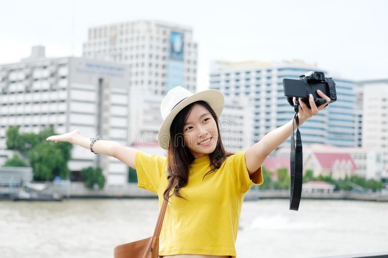 Young cute asian woman travler in casual style making camera selfie in the urban city outdoors background, woman selfie,  people stock photography