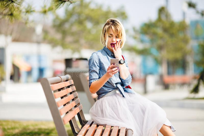 Young cute blond girl with short hair sitting on a wooden bench looks at smartphone and gets surprised wearing denim stock image