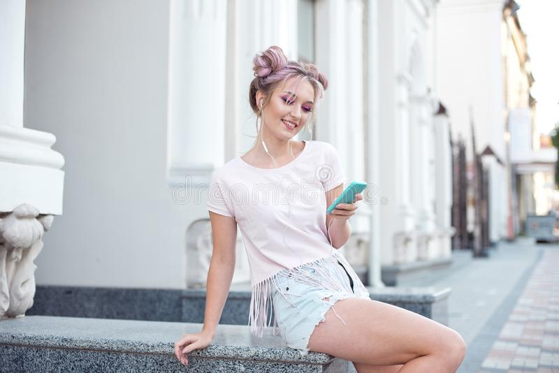 Young cute blonde and bright pink lips sitting on a bench, taking a selfie on her smartphone, in denim shorts, pink T royalty free stock photography