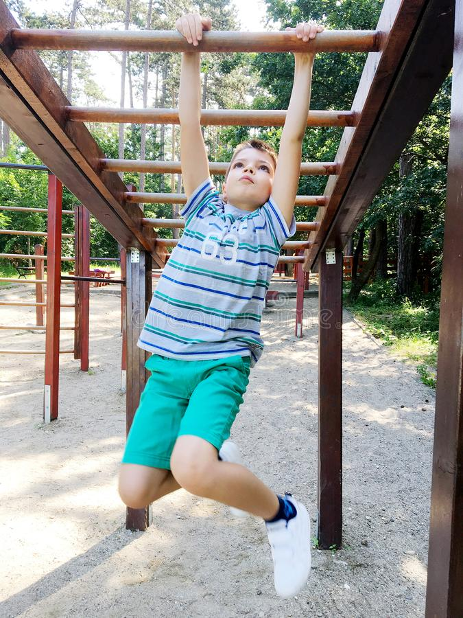 Young cute boy doing exercise in park. Young cute boy doing exercise the park .Sports concept stock photo