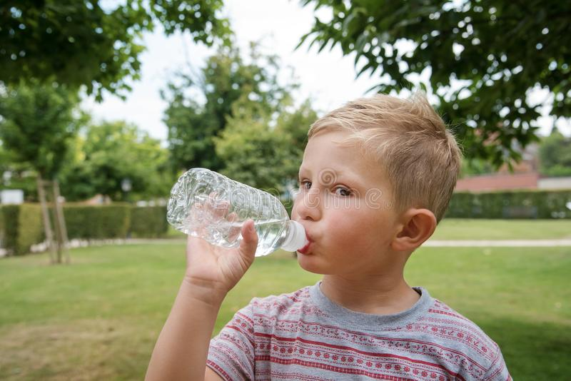 Young cute boy drinking water. Young boy drinking water, outdoor portrait royalty free stock images