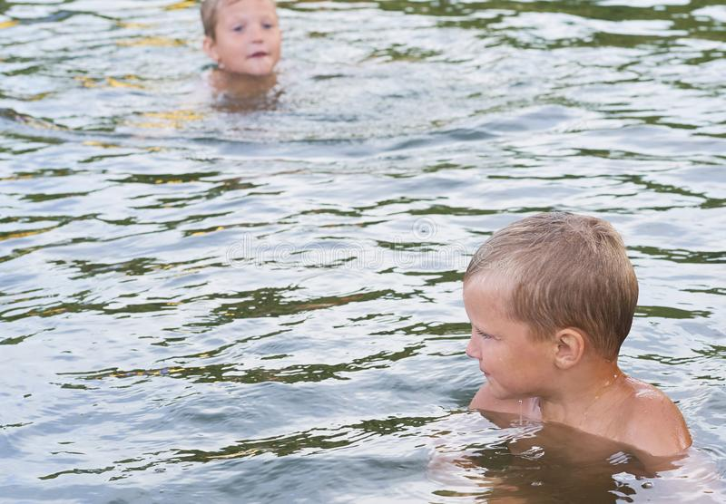 Young cute boy and his little brother playing in the water in a beautiful river or lake on a sunny summer day royalty free stock photos