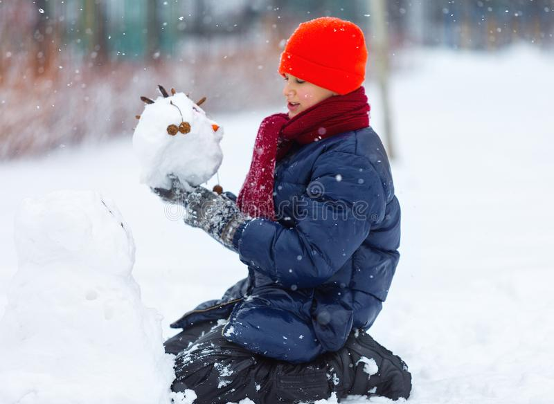 Young cute boy in orange hat sledding from a hill, plays snowballs, makes snowman on winter holidays. stock image