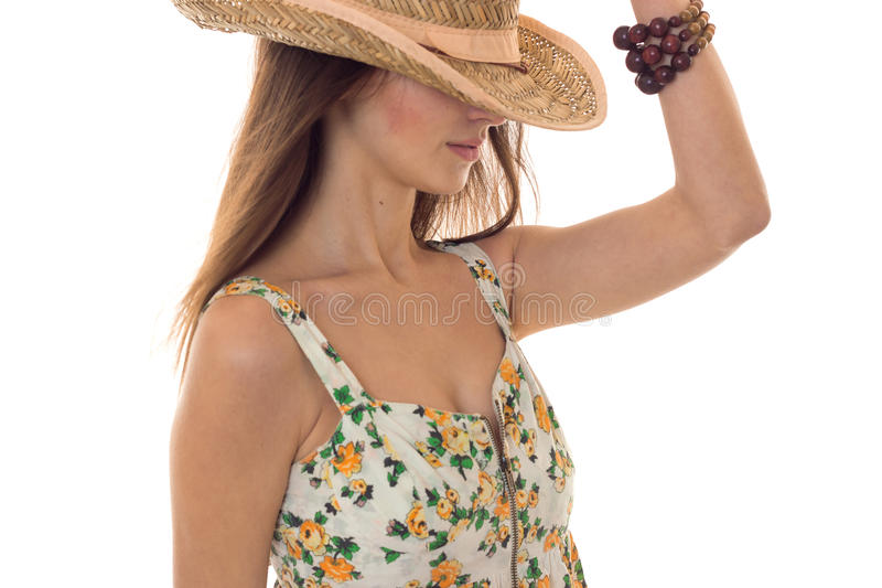 Young cute brunette girl in sarafan with floral pattern and straw hat with wide brim posing with hide eyes isolated on royalty free stock photo