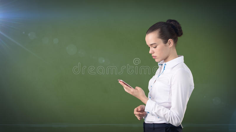 Young cute businesswoman close up portrait holding mobile phone in her hands and watching it. Isolated studio background royalty free stock photo
