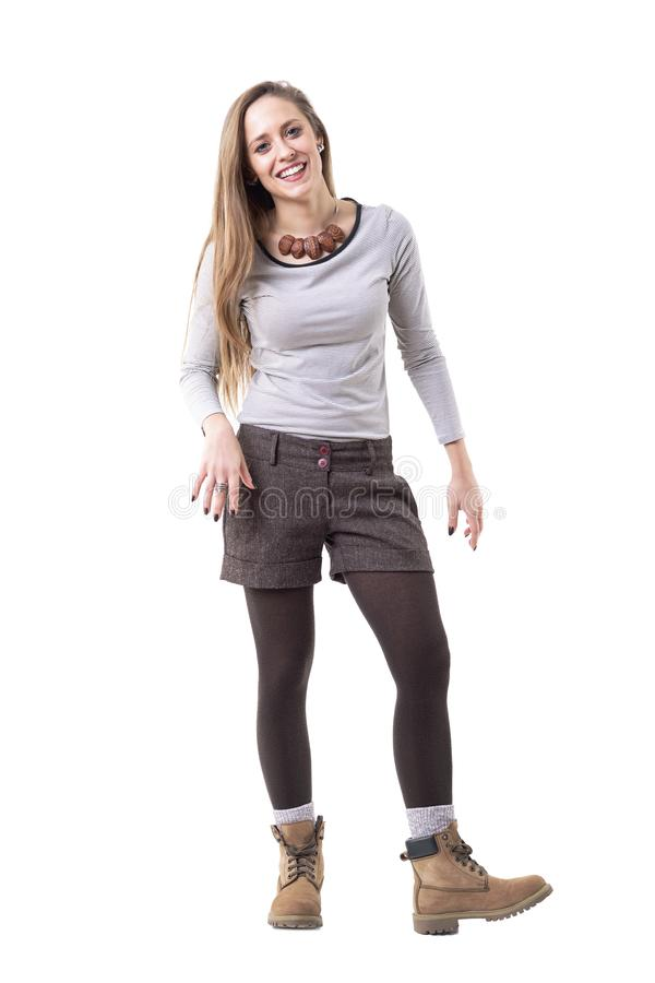 Young cute candid relaxed hipster girl laughing wearing leather ankle boots. royalty free stock image