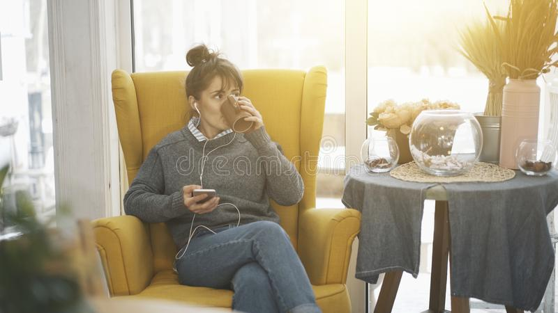 A young girl sitting in a big chair with a phone listening to music drinking tea stock photos
