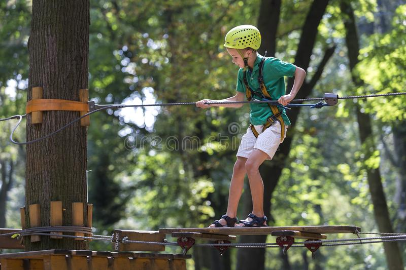 Young cute child boy in summer clothing, safety harness and helmet attached with carbine to cable moves slowly along rope way on. Green trees sunny bokeh stock photography
