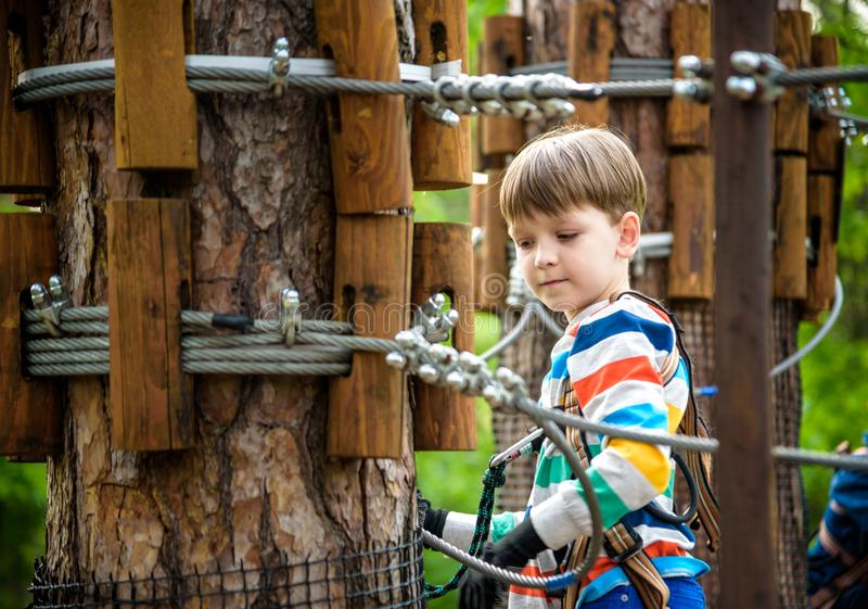 Young cute child boy in summer clothing, safety harness and helmet attached with carbine to cable moves slowly along rope way on. Green trees sunny bokeh royalty free stock photo