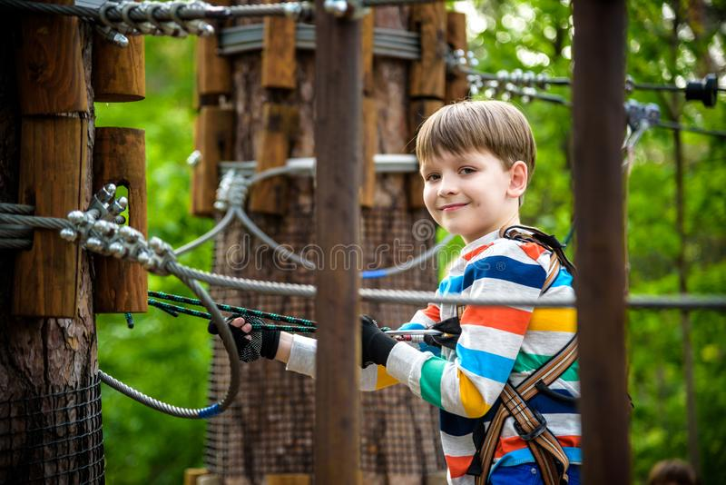 Young cute child boy in summer clothing, safety harness and helmet attached with carbine to cable moves slowly along rope way on. Green trees sunny bokeh stock photos