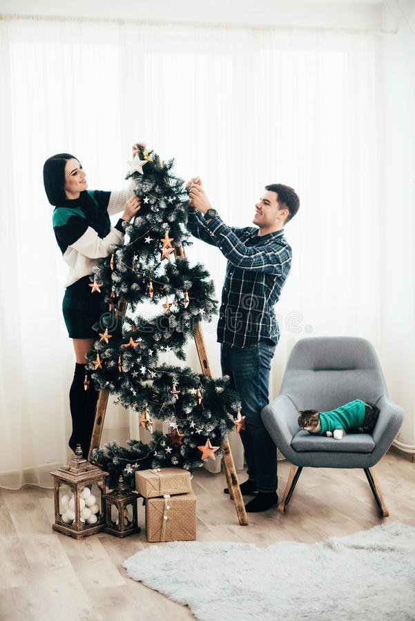 Young cute couple decorate a Christmas tree on Christmas Eve.  royalty free stock image