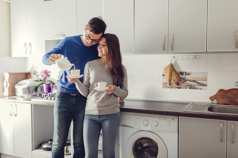 Young cute couple hugging and drinking tea in the kitchen. Young cute couple hugging and drinking tea in the kitchen stock image