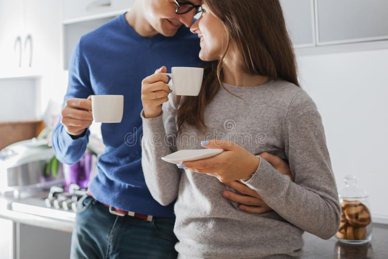 Young cute couple hugging and drinking tea in the kitchen.  royalty free stock photography