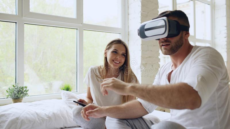 Young cute couple with tablet computer and virtual reality headset playing 360 VR video game while sitting in bed at stock image