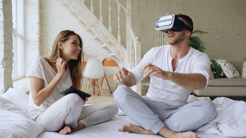 Young cute couple with tablet computer and virtual reality headset playing 360 VR video game while sitting in bed at stock photo