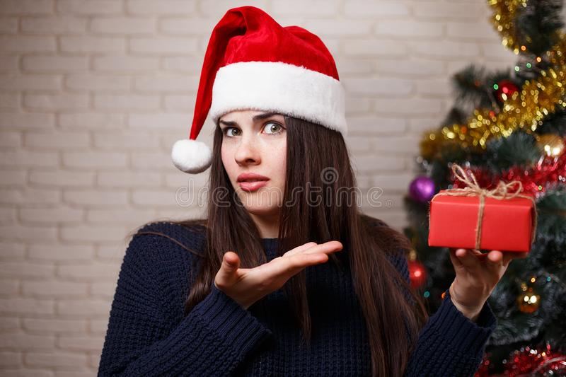 Young cute displeased woman in Santa cap is disappointed with he stock image
