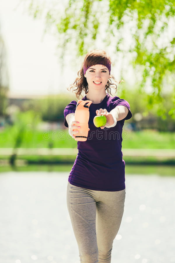 Young cute female athlete in a blue vest holding a bottle of water and an apple and looking at the camera royalty free stock photography