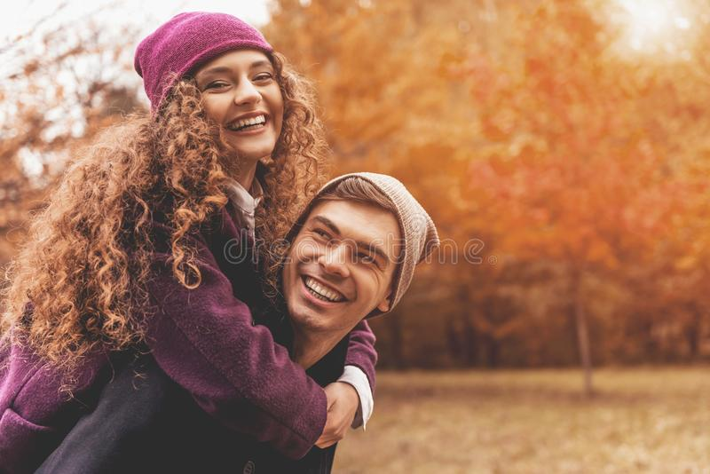Young Cute Female Hugs Boyfriend. In Autumn Outdoor. Lovers Walking in Park. Attractive Funny Couple. Lovestory in Forest. Man and Woman. Cute Lovers in the royalty free stock photos