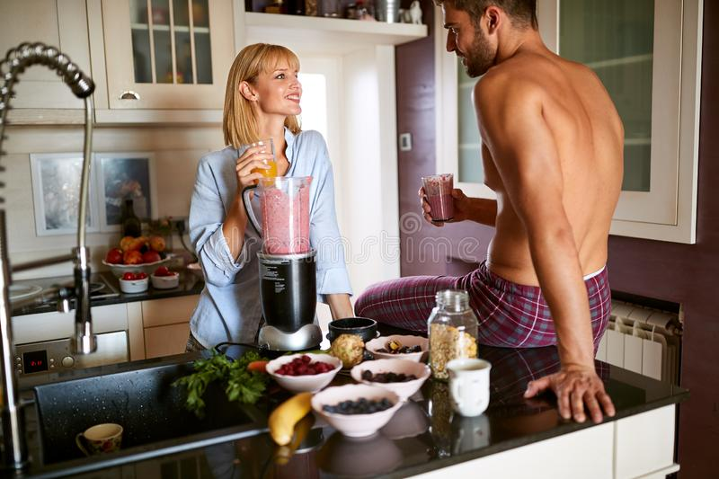 Young cute female with male in kitchen stock photography