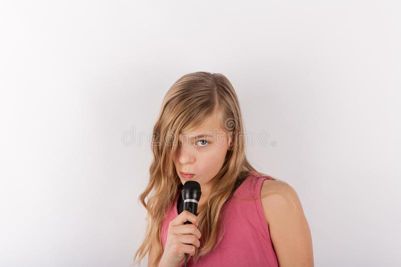 Young cute girl holding a microphone singing karaoke royalty free stock photos