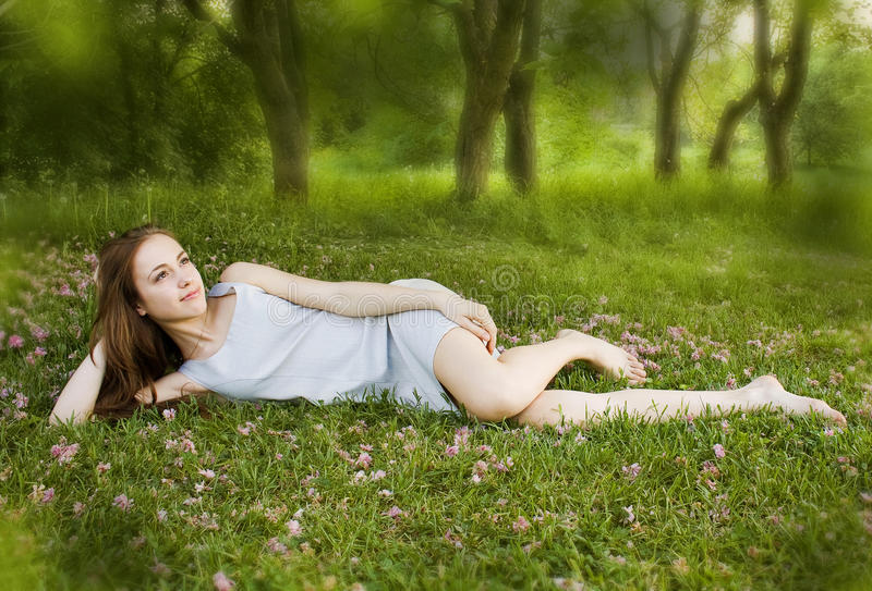 Young cute girl is leaning on the green gras stock photography