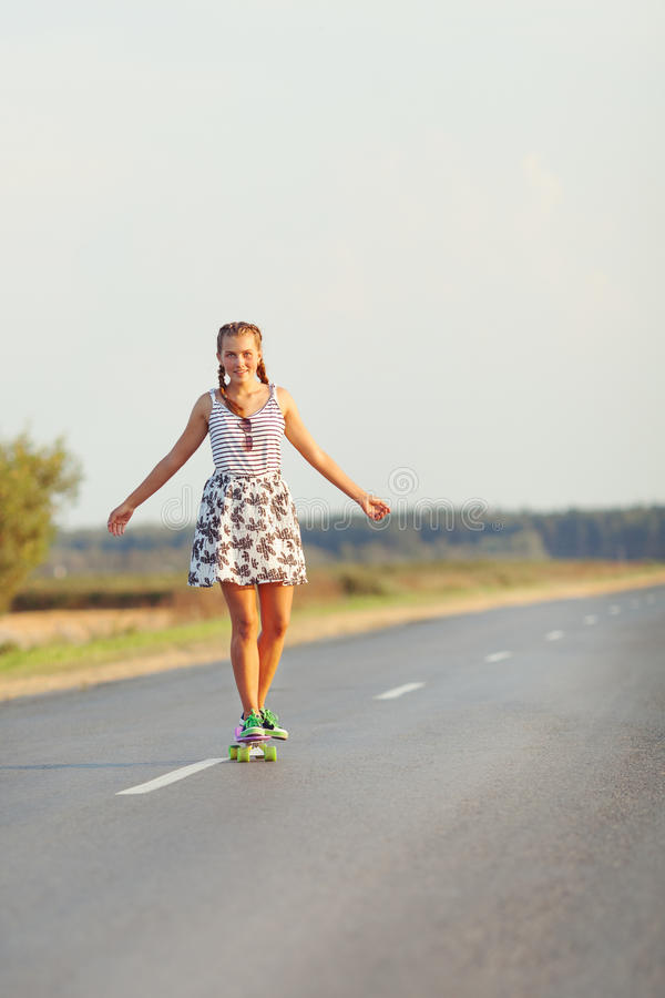 Young cute girl rides skateboard on road. Young happy cute girl rides skateboard on road, outdoor royalty free stock image