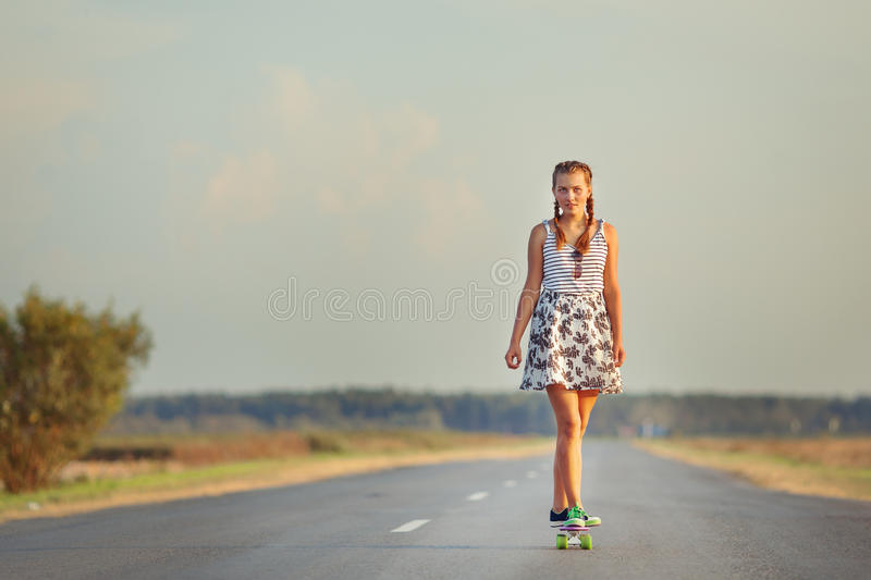 Young cute girl rides skateboard on road. Young happy cute girl rides skateboard on road, outdoor stock image