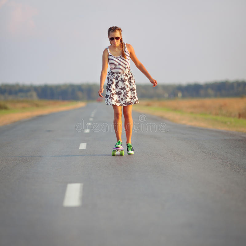 Young cute girl rides skateboard on road. Young happy cute girl rides skateboard on road, outdoor stock photography