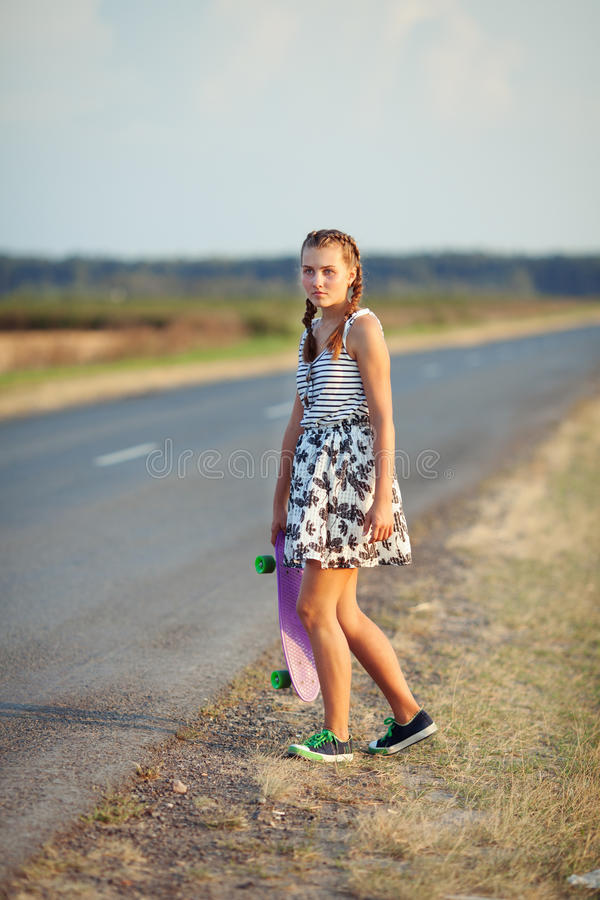 Young cute girl rides skateboard on road. Young happy cute girl rides skateboard on road, outdoor stock images