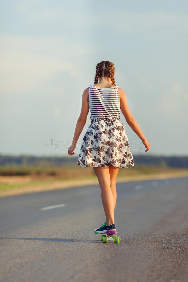Young cute girl rides skateboard on road. Outdoor stock photo