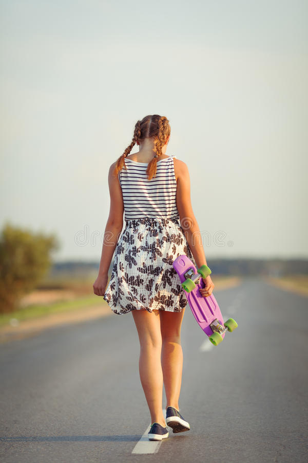 Young cute girl rides skateboard on road. Outdoor royalty free stock photos