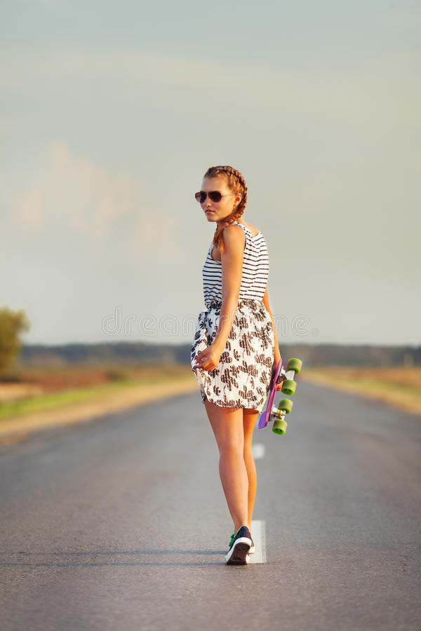 Young cute girl rides skateboard on road. Outdoor royalty free stock photo