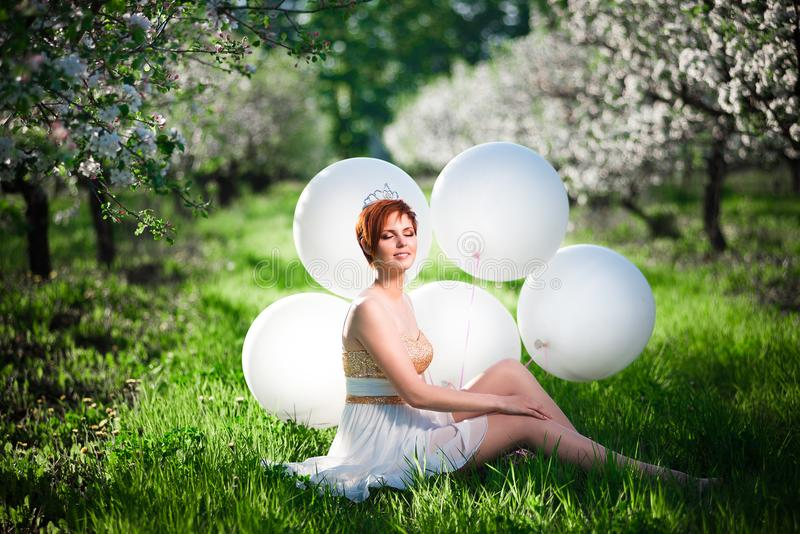 Young cute girl in a spring apple garden sitting stock photography