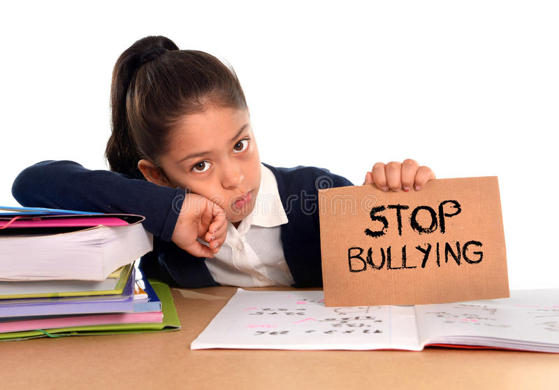 Young cute hispanic schoolgirl scared in stress holding paper with text stop bullying royalty free stock photos