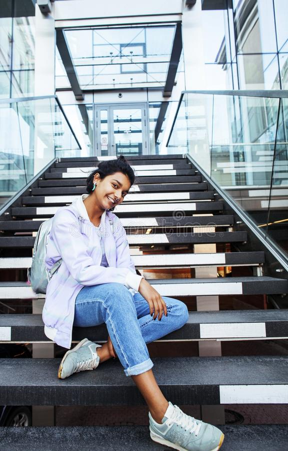 Young cute indian girl at university building sitting on stairs. Reading a book, wearing hipster glasses, lifestyle people concept close up stock photo