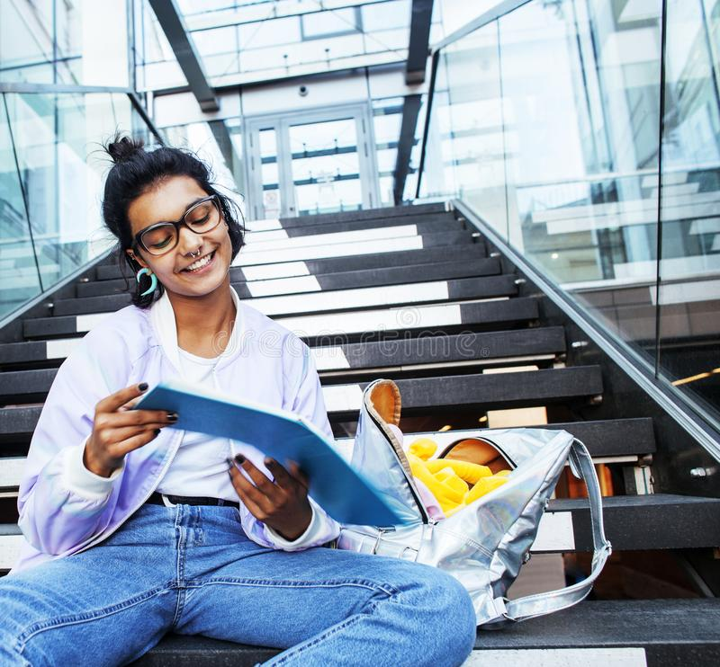 Young cute indian girl at university building sitting on stairs. Reading a book, wearing hipster glasses, lifestyle people concept close up royalty free stock photography