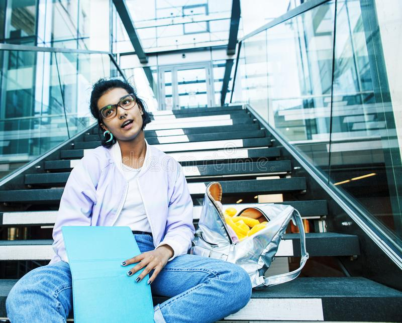Young cute indian girl at university building sitting on stairs. Reading a book, wearing hipster glasses, lifestyle people concept close up stock photos