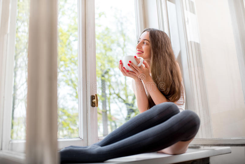 Young and cute lady sitting on the windowsill and looking out th. E window with cup of coffee in the morning stock photos