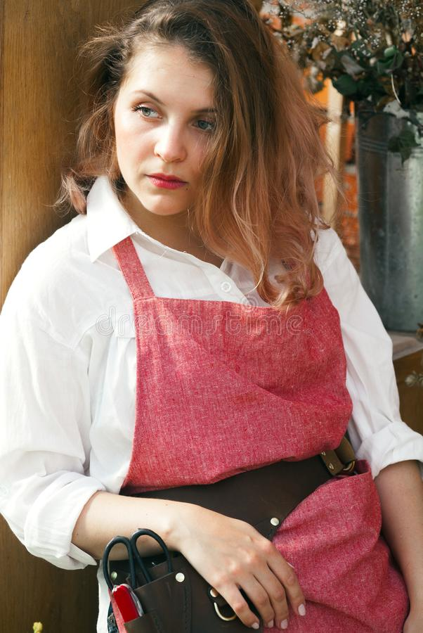Young cute lady working at the greenhouse. Wearing pink linen apron, white gloves and leather belt with florist tools. Rest after work day concept stock photos