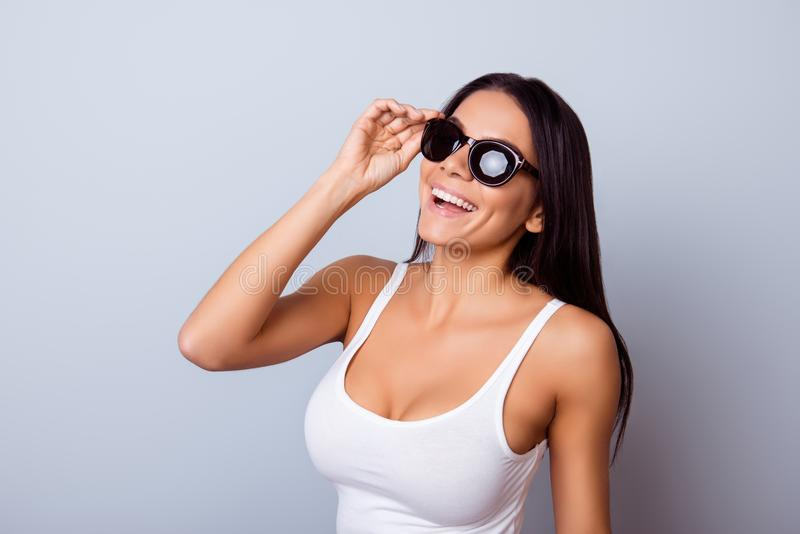 Young cute latin american lady with beaming smile in stylish spectacles is standing on the light blue background. She is full stock images
