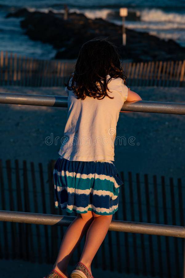 Young cute little girl on the boardwalk with back to camera looking towards the ocean surf royalty free stock photos